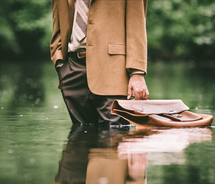 A man holding a briefcase standing in water.