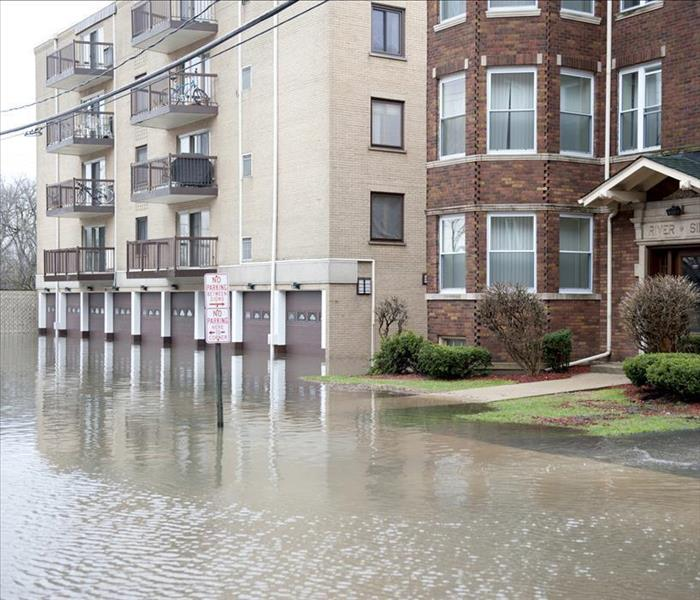 Apartment building flooded on the sidewalk up to garage doors.